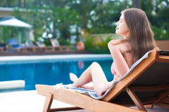 Happy young woman in bikini laying on chaise- Royalty Free Stock Images