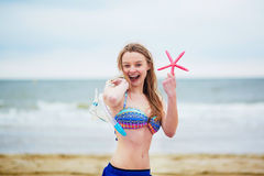 Happy young woman in bikini with snorkelling equipment and pink starfish Stock Photography