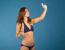 Happy young woman in bikini swimsuit and camera on green backgro Royalty Free Stock Photography