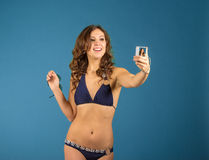 Happy young woman in bikini swimsuit and camera on green backgro Royalty Free Stock Image