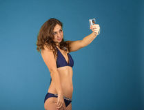 Happy young woman in bikini swimsuit and camera on green backgro Stock Photo