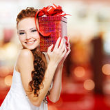Happy young woman with birthday present in hands. Posing indoors royalty free stock photos