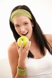 Happy young woman biting apple Stock Photo