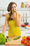 Happy young woman biting cucumber while cutting fresh salad Royalty Free Stock Images