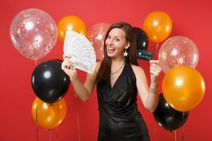Happy young woman in black dress celebrating holding credit card, bundle lots of dollars, cash money on red background