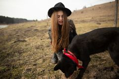 Happy young woman with black hat, plaing with her black dog on the shore of the lake stock image