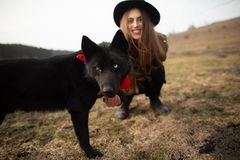 Happy young woman with black hat, plaing with her black dog on the shore of the lake royalty free stock photography