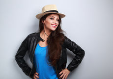 Happy young woman in black jacket and straw hat posing Stock Images