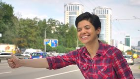 Happy young woman with black short hair lifting thumb and looking for taxi, standing on street near road in urban city stock video
