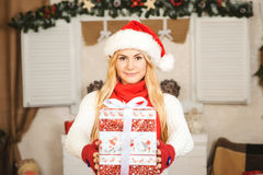 Happy young woman blonde holding a Christmas present box. Royalty Free Stock Photos