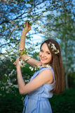 Happy young woman with blooming cherry tree in spring garden Royalty Free Stock Images