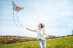 Happy young woman on a blooming spring clearing launches a kite. Summer, spring, vacations, nature, freedom, dreams, concept Royalty Free Stock Photo