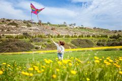 Happy young woman on a blooming spring clearing launches a kite. Summer, spring, vacations, nature, freedom, dreams, concept Royalty Free Stock Photos