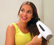 Happy young woman blow drying hair in bathroom.  royalty free stock photos
