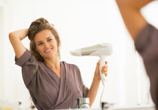 Happy young woman blow drying hair in bathroom Royalty Free Stock Images