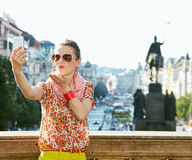 Happy young woman blowing air kiss and taking selfie in Prague Royalty Free Stock Image