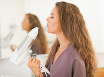 Happy young woman blowing on blow dryer Stock Images
