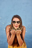 Happy young woman blowing confetti in the air Royalty Free Stock Image