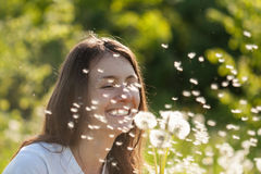 Happy young woman blowing at dandelions Royalty Free Stock Photos