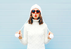 Happy young woman blowing red lips makes air kiss wearing a heart shape sunglasses, knitted hat, sweater over blue Stock Photo