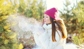 Happy young woman blowing snow on hands in winter Royalty Free Stock Photography