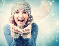 Happy young woman blowing snow. In snowy day Stock Photo