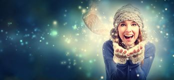 Happy young woman blowing snow. In snowy night Royalty Free Stock Photography