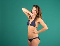 Happy young woman in blue bikini swimsuit posing Royalty Free Stock Image