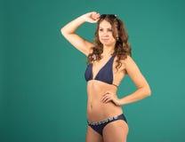Happy young woman in blue bikini swimsuit posing Stock Photography