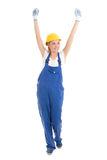 Happy young woman in blue builder uniform with hands up isolated Royalty Free Stock Photo