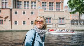 A happy woman is standing against the background of typical Belgian houses in Bruges, Belgium. royalty free stock image