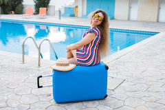 Happy young woman with blue luggage arriving to the resort. She is walking next to the swimming pool. Beginning of Stock Photo