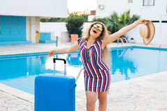 Happy young woman with blue luggage arriving to the resort. She is walking next to the swimming pool. Beginning of Royalty Free Stock Photo