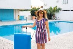 Happy young woman with blue luggage arriving to the resort. She is walking next to the swimming pool. Beginning of Royalty Free Stock Image