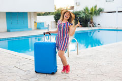 Happy young woman with blue luggage arriving to the resort. She is walking next to the swimming pool. Beginning of Stock Images