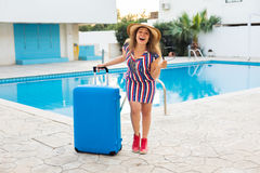Happy young woman with blue luggage arriving to the resort. She is walking next to the swimming pool. Beginning of Royalty Free Stock Images