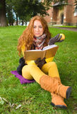 Happy young woman with book and apple Stock Photo