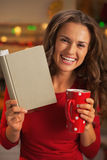 Happy young woman with book cup of hot chocolate Stock Image