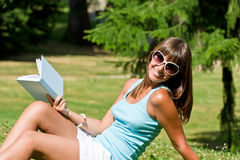 Happy young woman with book in park Royalty Free Stock Image