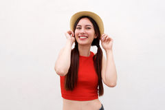 Happy young woman with both hands on hat. Portrait of happy young woman with both hands on hat Stock Photography
