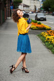Happy young fashion woman in yellow blouse and blue skirt royalty free stock images