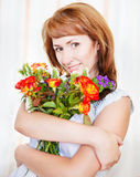 Happy young woman with bouquet of spring flowers Stock Photos