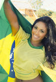 Happy young woman in Brazil football top. Pretty happy beautiful young woman wearing Brazil soccer football top holding Brazilian national flag.  Concept Image Stock Images