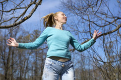 Happy young woman in bright clothes jumps in spring park Royalty Free Stock Photography