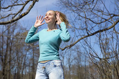 Happy young woman in bright clothes jumps in spring park Stock Photography