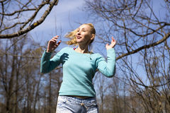 Happy young woman in bright clothes jumps in spring park Royalty Free Stock Photos