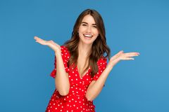 Happy young woman with bright smile in red casual dress looking up with excited face with hands up over blue background.