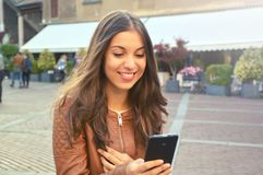 Happy young woman with brown jacket reading a message on smart phone urban background stock photo