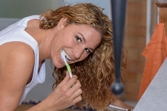 Happy young woman brushing her teeth Stock Image