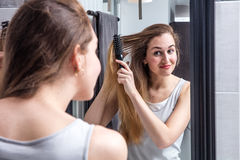 Happy young woman brushing long hair in front of mirror royalty free stock photography